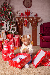 beautiful little girl with gifts near a Christmas tree