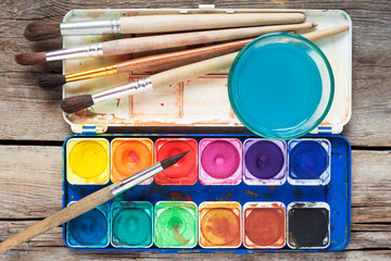 Set of watercolor paints, art brushes and glass of water on old