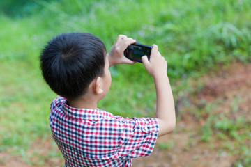 Little boy taking photos by digital camera on smartphone with go