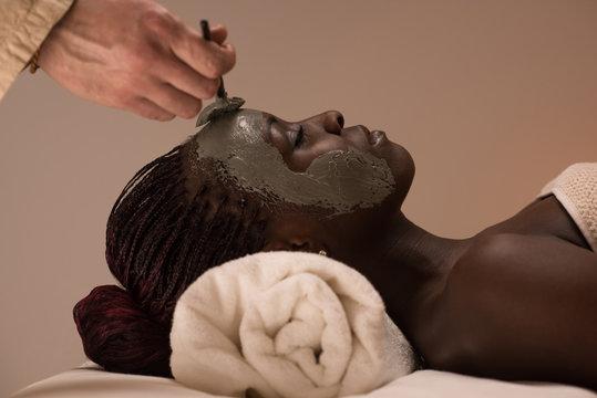 African woman having clay facial mask