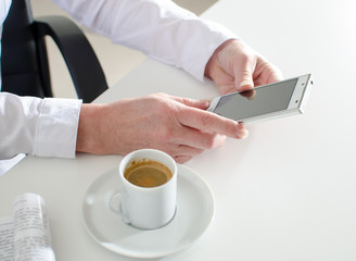 Businesswoman using a smartphone during coffee break