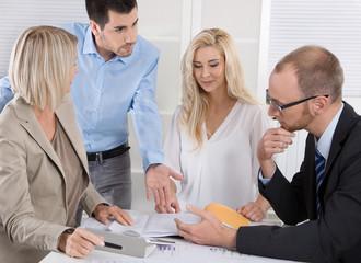 Männer und Frauen sitzen in einer Gruppe in einem Meeting