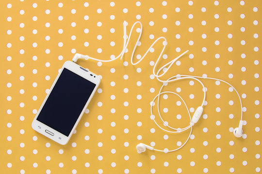 Small headphones with mobile phone on yellow vintage paper with