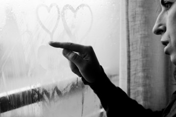 woman drawing heart on wet window