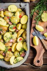 Preparing baked potatoes with herbs and garlic