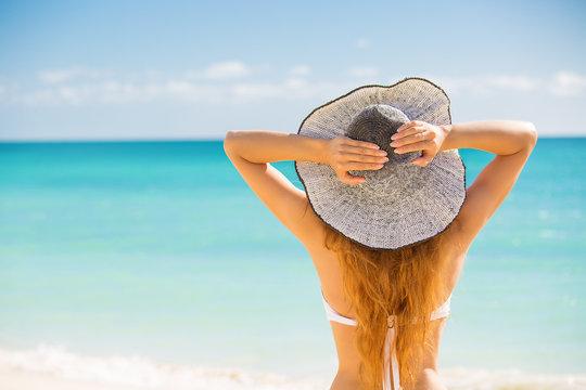 Woman enjoying beach relaxing joyful in summer by tropical ocean
