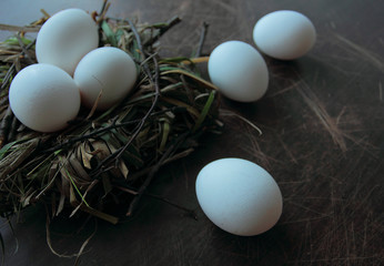 Eco eggs on the nest and on a wooden background.