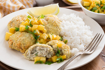 fish cakes with mango salsa and rice, close-up