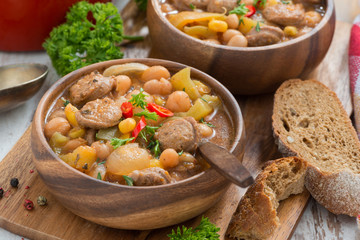 vegetable stew with sausages in a wooden bowl on board and bread