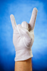 Hand in white glove showing horn sign