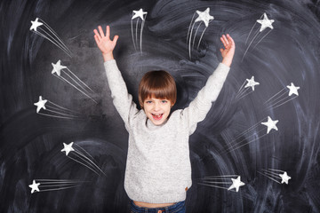 The boy raised his hands to the top and on the chalkboard stars