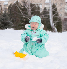 Cute baby boy playing in park in winter