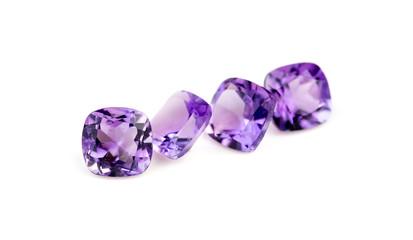 Natural purple amethyst gemstones isolated on white