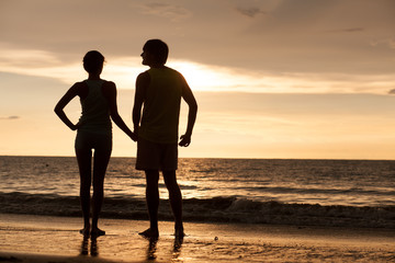 sunset silhouette of young couple in love walking at beach