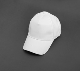 White baseball cap on gray background.