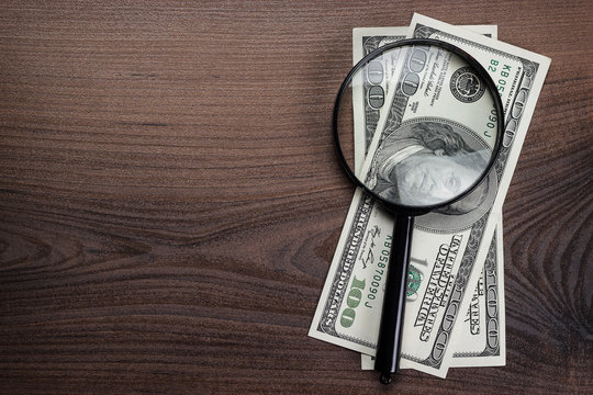 magnifying glass and money on wooden background