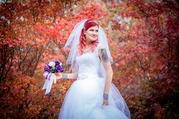 Red-haired bride on a background of red trees