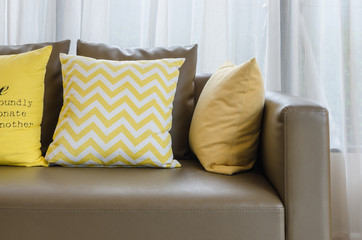 brown modern sofa with yellow pillows