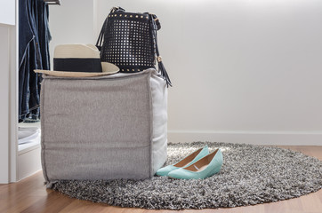 hat and bag on chair with shoes on carpet