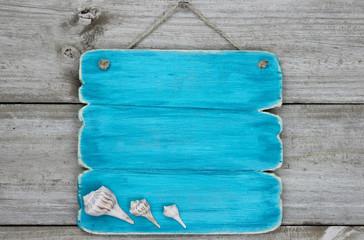 Blank blue sign with seashells hanging on door