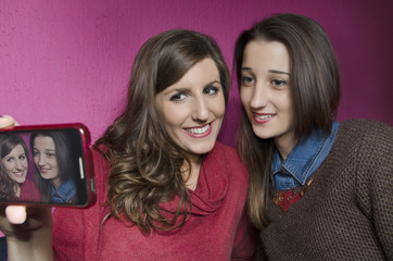 Two beautiful girls taking a selfie photo indoors.