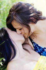 Caucasian And Asian American Women Kissing Outdoors