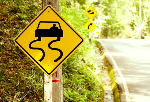 Caution of slippery roads - traffic signs beside country road