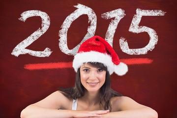 Composite image of festive brunette leaning on large poster