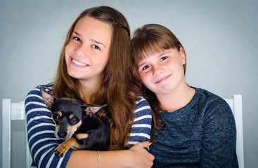 Studio portrait of sisters with dog