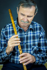Man playing on pipe flute