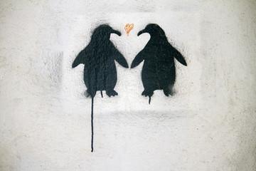 graffiti art depicting two black penguins in love.