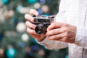 Man holding retro camera against Christmas background