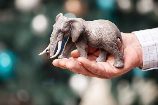 Male hand with toy elephant over Christmas background