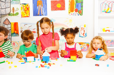 Group of happy kids play with plastic blocks
