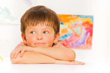 Thoughtful portrait of little boy lay on the table