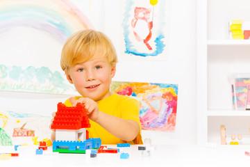 Handsome blond boy building house