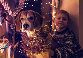 Boy with his dog sitting on decorated window for Christmass Eve