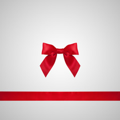 Red ribbon bow on grey background.