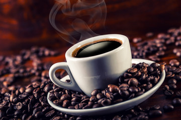 Cup of black coffee and spilled coffee beans. Coffee break