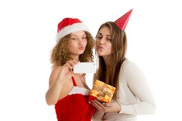 Two girls blow a kiss while taking selfie in cristmas costumes