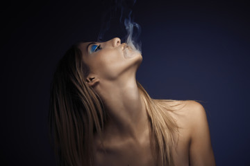 Portrait of young sexy woman while smoking cigarette
