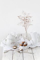 tea time with coconut sweets and dried flowers on white table