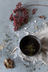 cup of thyme infusion on table with red berries branch