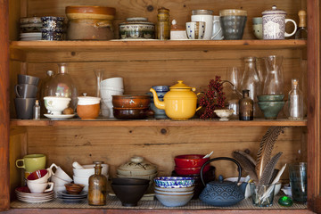 ceramics and kitchen equipment on rustic wooden shelves
