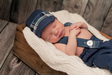 Newborn Baby Boy Wearing a Newsboy Cap and Suspenders