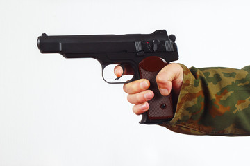 Hand in camouflage uniform with gun on a white background