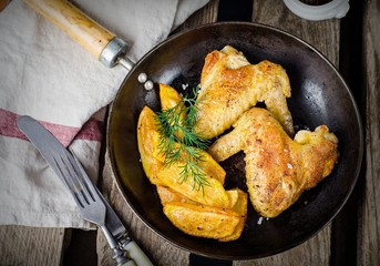Roasted chicken wings with fried potatoes and ketchup in iron pot on wooden vintage background