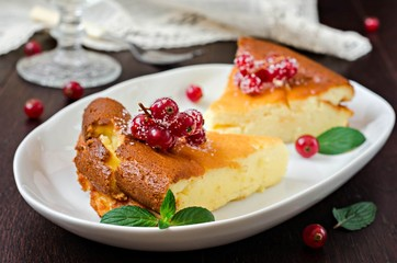 Cottage cheese casserole with freshly berries in white plate on wooden table