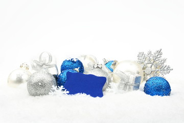 Silver and blue christmas decoration on snow with wishes card