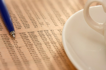 Closeup of a cup of coffee and a pen on a morning newspaper